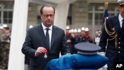 Le président français François Hollande décore à titre posthume l'officier de police tué Xavier Jugelé abattu sur les Champs-Élysée, au siège de la police de Paris, France, 25 avril 2017.