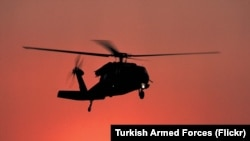 Silhoutte of a Turkish Army utility helicopter in an undisclosed location, either an S-70 or UH-60 Black Hawk