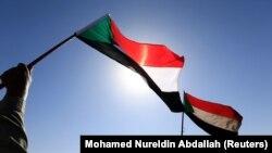 Warga Sudan sedang mengibarkan bendera negaranya di Khartoum, Sudan, 9 Januari 2019. (Foto: REUTERS/Mohamed Nureldin Abdallah)