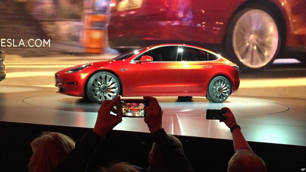 FILE - Tesla Motors unveils the new lower-priced Model 3 sedan at the Tesla