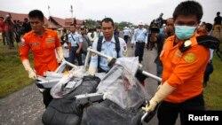 5일 인도네시아 구조팀이 자바해에서 발견된 사고 여객기 파편을 운반하고 있다.
