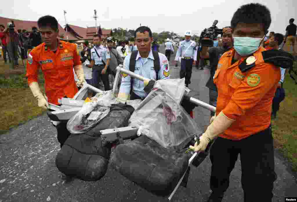 Parts of AirAsia Flight 8501, recovered from the Java Sea, are carried after they were offloaded from a U.S. Navy helicopter at the airport in Pangkalan Bun, Central Kalimantan, Indonesia,  Jan. 5, 2015.