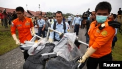 Parts of AirAsia QZ8501, recovered from the Java Sea, are carried by Indonesian Airforce and Search and Rescue crew members after they were offloaded from a U.S. Navy helicopter at the airport in Pangkalan Bun, Central Kalimantan January 5, 2015. Indonesi
