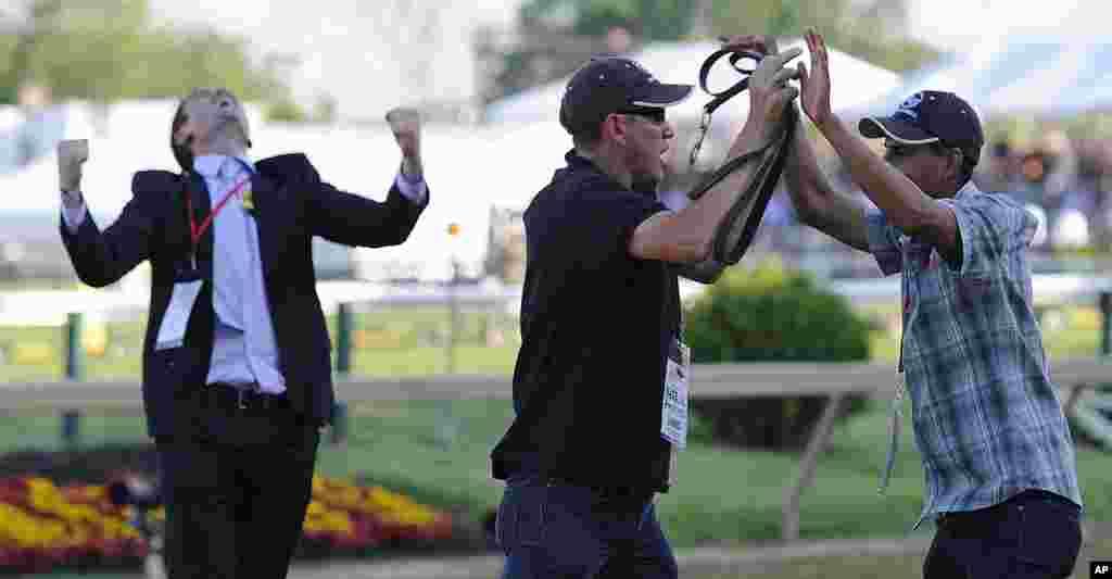 """Los cuidadores de """"I´ll Have Another"""" Inocencio Diaz y Benjamin Pérez celebran la victoria en el Preaknnes junto a Jack Sistrunk. (AP)"""