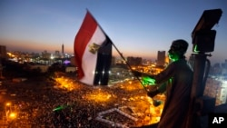 An Egyptian protester waves a national flag over Tahrir Square, the focal point of Egyptian uprising as opponents of President Mohamed Morsi are gathered in Cairo, June 28, 2013.