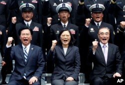 FILE - Taiwan's President Tsai Ing-wen, center, along with Defense Minister Feng Shih-kuan, right, and Secretary-General of National Security Council Joseph Wu, left, cheer with navy officers during a visit to Zuoying Naval base in Kaohsiung, southern Taiwan.