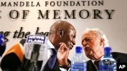 El juez Dikgan Moseneke conversa con George Bizos, durante una conferencia de prensa para explicar el testamento de Mandela.