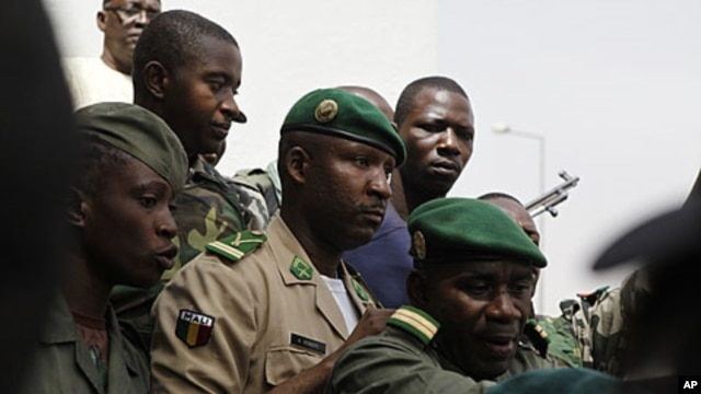 Lieutenant Amadou Konare, centre, spokesman for coup leader Amadou Haya Sanogo, unseen, is surrounded by security as he arrives to address supporters, as thousands rallied in a show of support for the recent military coup, in Bamako, Mali, March 28, 2012.