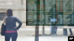 A stock exchange monitor displays the market trends in Milan, Italy, November 9, 2011.