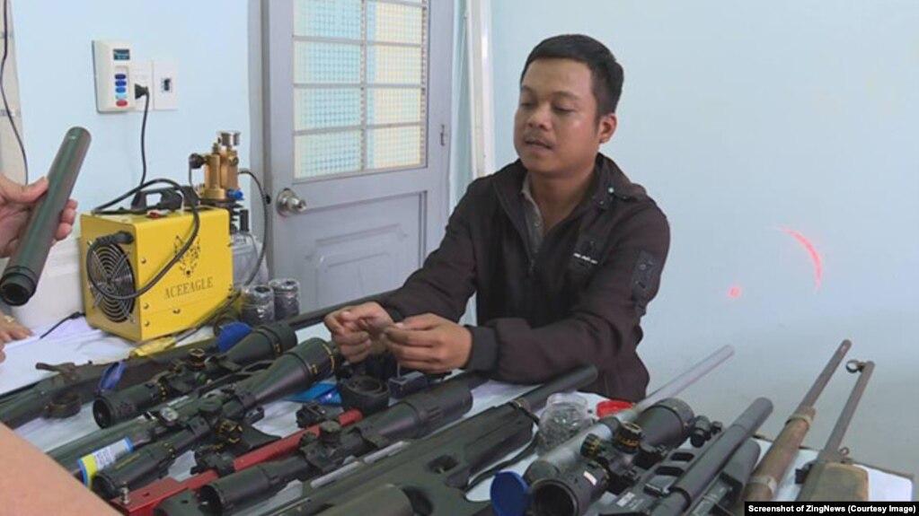 Nguyễn Quốc Thắng cùng tang vật là các khẩu súng tự chế. (Ảnh chụp màn hình ZingNews)
