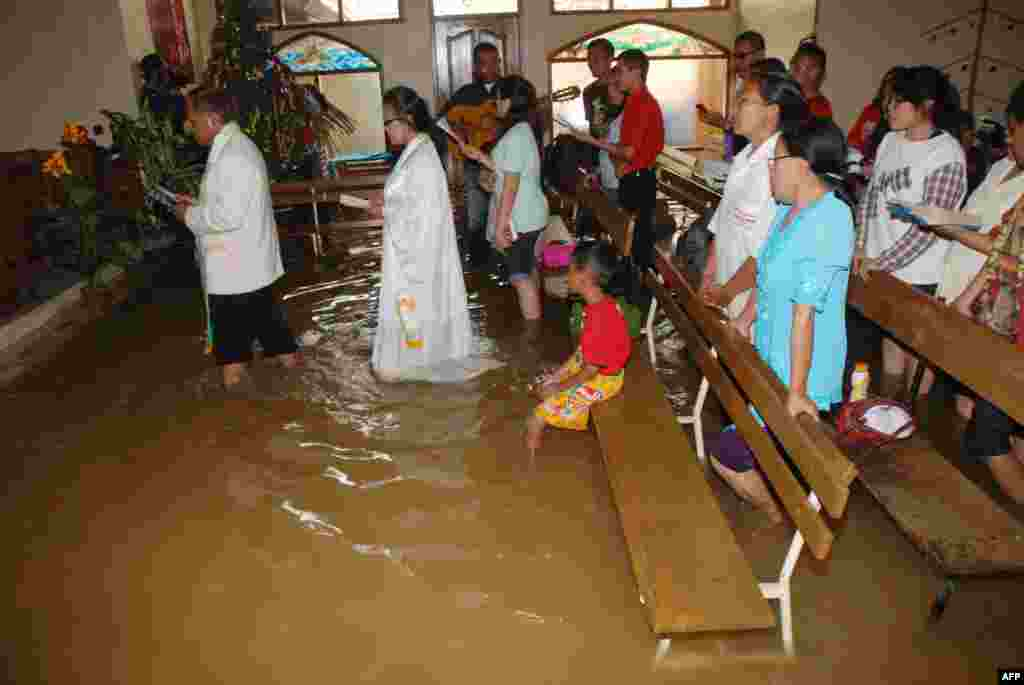Christians attend the mass service at a flooded church in Bandung, in western Java island, Indonesia, Dec. 25, 2014.