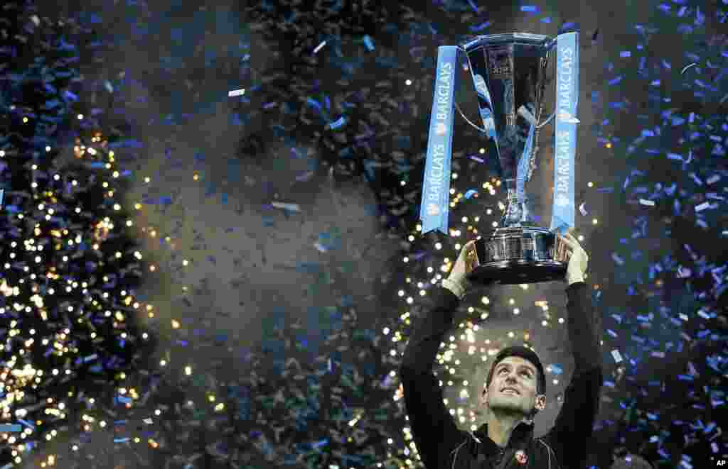 Novak Djokovic of Serbia holds up the ATP World Tour Finals tennis trophy after defeating Rafael Nadal of Spain at the O2 Arena in London, Nov. 11, 2013.