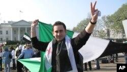 一位抗议者领袖在白宫前展开一面叙利亚旗帜,呼吁美国采取行动保护叙利亚平民