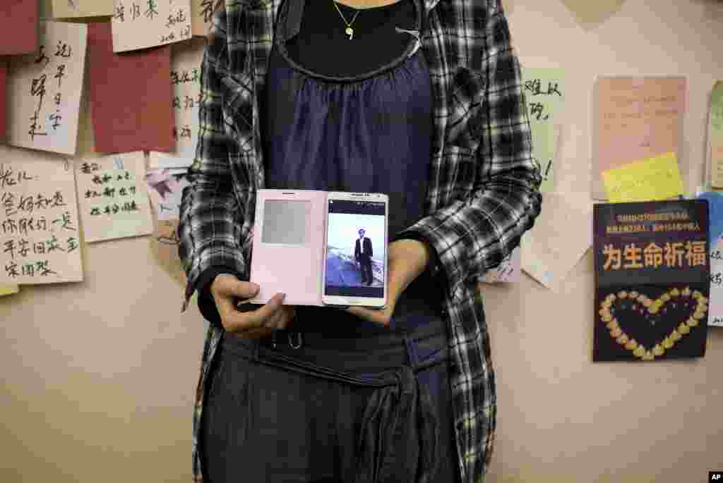 A woman, the daughter of a Chinese passenger on Flight MH370 shows her mobile phone displaying a photo of her father near the wall displaying messages of wishes for the passengers at a hotel in Beijing, April 11, 2014.