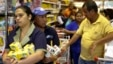 People hold their groceries as they line up to pay the cashier at a supermarket in Caracas, Veneuela, Aug. 21, 2014.