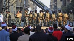 Beberapa tentara Mesir membuat barikade untuk menjaga kantor Kementerian Dalam Negeri sementara para demonstran memandangi mereka (24/11).