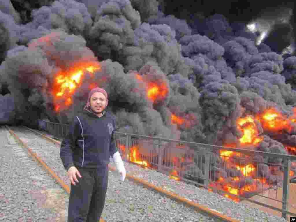 An anti-Syrian regime activist in front of flames and black smoke from a bombed oil pipeline in Homs, February 15, 2012. (AP/Local Coordination Committees)