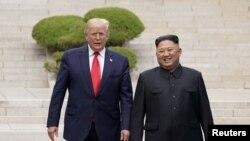 도널드 트럼프 미국 대통령과 김정은 북한 국무위원장이 지난 6월 30일 판문점 회동에서 군사분계선을 함께 넘고 있다.