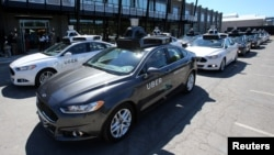 FILE - A fleet of Uber's Ford Fusion self-driving cars are shown during a demonstration of self-driving automotive technology in Pittsburgh, Pennsylvania, Sept. 13, 2016.