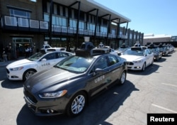 FILE - A fleet of Uber's Ford Fusion self-driving cars is shown during a demonstration of self-driving automotive technology in Pittsburgh, Sept. 13, 2016.
