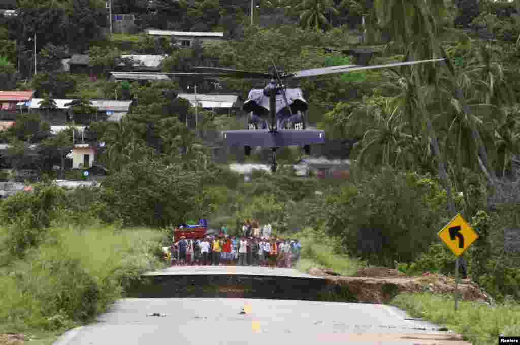 People wait as a helicopter lands on a collapsed road in Coyuca de Benitez, about 35 km (22 miles) from Acapulco, Sept. 17, 2013. Mexico's famous beach resort of Acapulco was in chaos as hotels rationed food for thousands of stranded tourists and floodwaters swallowed homes and cars after some of the most damaging storms in decades killed at least 55 people across the country.