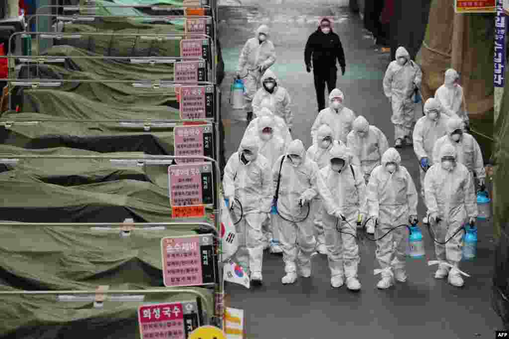Workers wearing protective gear spray disinfectant at a market in the southeastern city of Daegu, South Korea, as a preventive measure after the COVID-19 coronavirus outbreak. South Korea reported two additional deaths from coronavirus and 123 more cases.