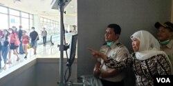 Gubernur Jawa Timur Khofifah Indar Parawansa mengamati monitor pemantau suhu tubuh penumpang pesawat yang baru tiba di Bandara Juanda (foto Petrus Riski/VOA)