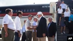 Le candidat républicain Donald Trump, suivi de son colistier Mike Pence, est accueilli par le procureur général de la Louisiane Jeff Landry à l'aéroport de Baton Rouge, 19 août 2016.