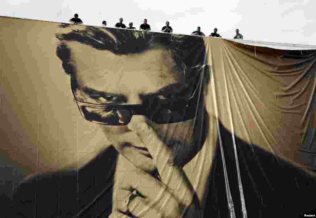 Workers set up a giant canvas of the official poster of the 67th Cannes Film Festival featuring actor Marcello Mastroianni on the Festival Palace in Cannes.