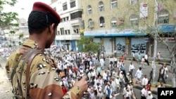 Binh sĩ đứng nhìn người biểu tình chống chính phủ tuần hành đòi lật đổ Tổng thống Yemen Ali Abdullah Saleh, 26/4/2011