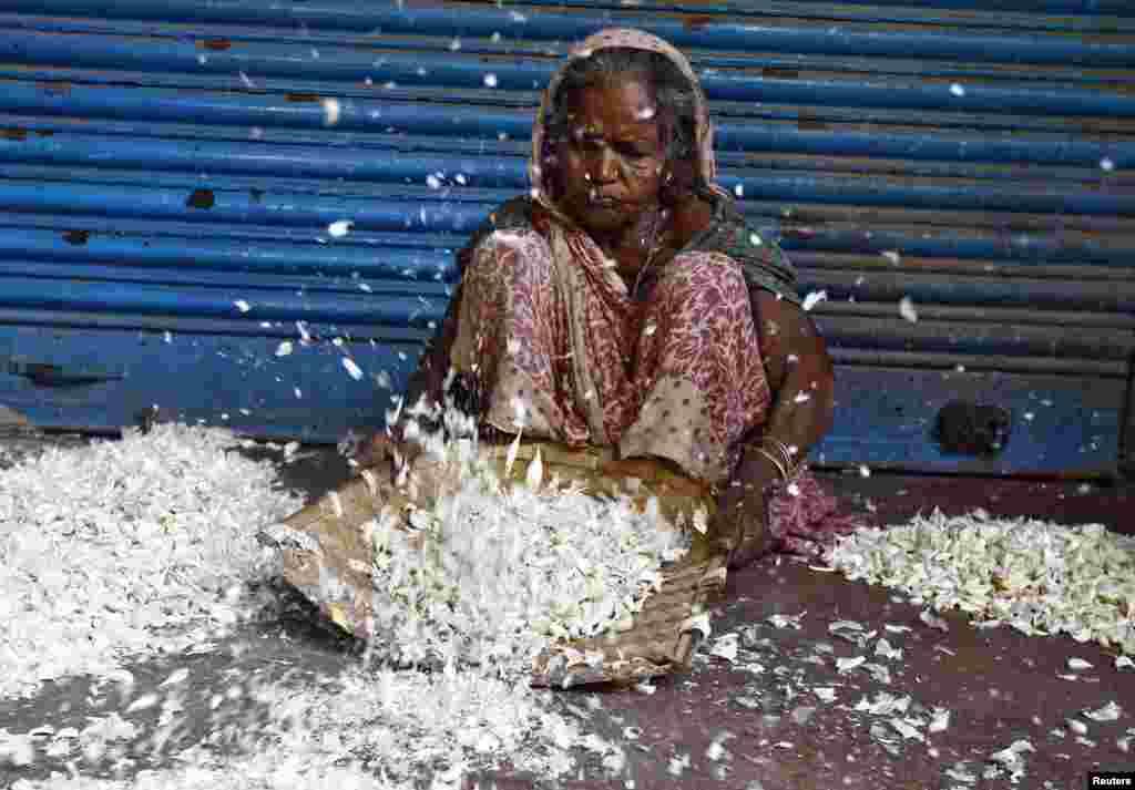 A laborer removes the skin of garlic at a wholesale market in Kolkata, India.