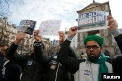 """Thanh niên Hồi giáo Pháp giơ các biểu ngữ có nội dung """"Tôi là người Hồi giáo. Tôi yêu Đấng Tiên tri của tôi"""" (phải) và """"Tôi là Muhammad. Tôi thuộc về cộng đồng Hồi giáo và tôi phản đối khủng bố"""" trong một cuộc diễu hành ở trung tâm Paris 18/1/2015."""