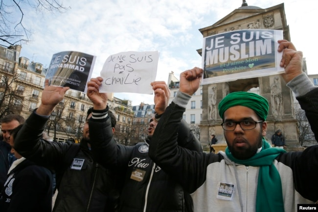 """FILE - French Muslim youths hold placards which read, """"I am Muslim. I love my Prophet"""" (R) and """"I am Muhammad. I belong to the Muslim community and I am anti-terrorist"""" during a demonstration in central Paris, Jan. 18, 2015."""