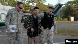 U.S. military servicemen assist freed Australian national Warren Richard Rodwell after he gets off a helicopter inside a military camp in Zamboanga City, southern Philippines, March 23, 2013, in this picture provided by the Western Mindanao Command of the