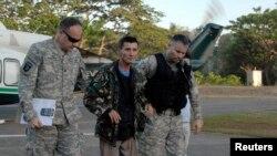 Tentara AS mengawal Warren Richard Rodwell, mantan seorang tentara Australia yang dibebaskan oleh penculiknya, turun dari helikopter di kompleks militer Zamboanga, Filipina, Sabtu (23/3). Rodwell diculik kelompok militan Abu Sayaf bulan Desember 2011 dari rumahnya di Pagadian barat, kepulauan Minadno, Filipina.