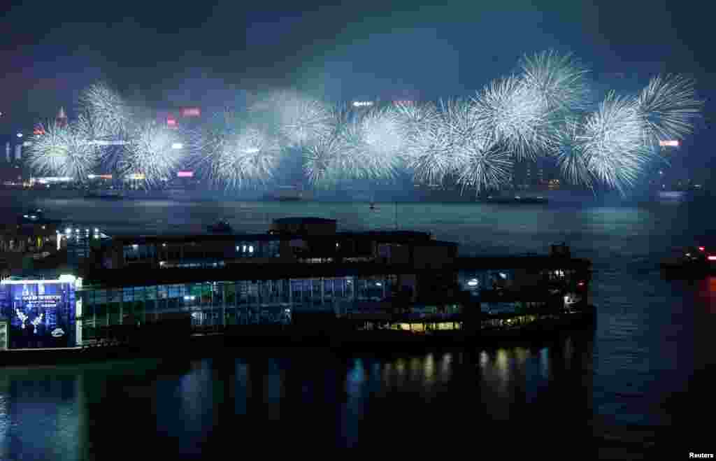 Fireworks explode over a cloudy Victoria Harbour during Lunar New Year celebrations in Hong Kong, China.