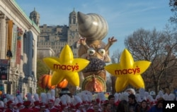 Performers stand in front of balloons at the start of the Macy's Thanksgiving Day Parade, in New York, Nov. 26, 2015.