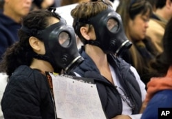FILE - Protesters wearing gas masks, attend a hearing about a gas leak at the southern California Gas Company's Aliso Canyon Storage Facility near the Porter Ranch section of Los Angeles. The Los Angeles County Department of Public Health released results May 13, 2016, that showed barium, manganese and vanadium were found more frequently and in higher concentrations in homes in the Porter Ranch area.
