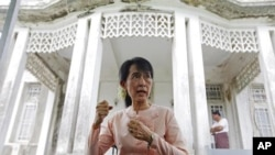 Pro-democracy leader Aung San Suu Kyi talks to reporters about her trip to Bagan, at her home in Yangon, July 11, 2011