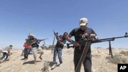 Wapiganaji waasi nchini Libya wakifyatuliana risasi na majeshi yanayomtii Moammar Gadhafi, nje ya mji wa Kikla, kiasi cha kilomita 40 kutoka mji wa Gheryene nchini Libya