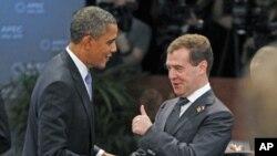 ປະທານາທິບໍດີຣັດເຊຍ ທ່ານ Dmitry Medvedev (ຂວາ) ຍົກໂປ້ໃຫ້ປະທານາທິບໍດີສະຫະລັດ ທ່ານບາຣັກ ໂອບາມາ ໃນຂະນະທີ່ພວກທ່ານພົບປະກັນໃນກອງປະຊຸມຄົບຄະນະເທື່ອທຳອິດໃນລະຫວ່າງກອງປະຊຸມສຸດຍອດ APEC ທີ່ນະຄອນໂຮໂນລູລູ ລັດຮາວາຍ (13 ພະຈິກ 2011)