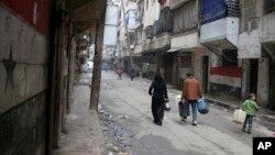 En esta foto de archivo civiles caminan con contenedores de agua y combustible en Alepo, Siria, el 11 de febrero de 2016.