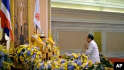 In this photo released by Thai Spokesman Office, Gen. Prayuth Chan-ocha pays a respect to a royal endorsement, black book seen at center, in front of the portrait of King Bhumibol Adulyadej as he accepted the written royal command issued by the King cert