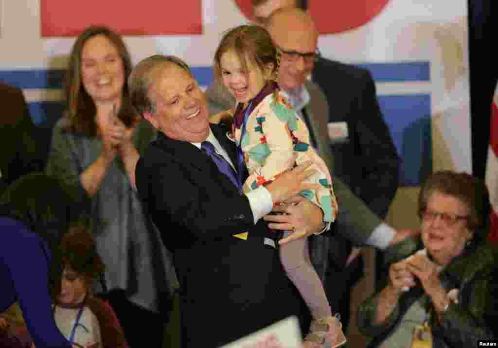 داگ جونز، سناتور منتخب آلاباما پیروزی غیرقابل انتظار خود را به همراه نوه اش در جمع هواداران جشن می گیرد.