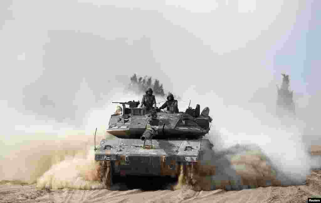 Israeli soldiers ride atop a tank outside the southern Gaza Strip, July 7, 2014.