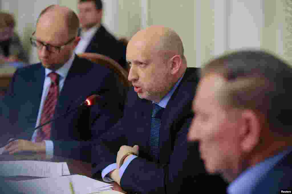 Acting Ukrainian President Oleksander Turchinov (center) and Prime Minister Arseny Yatseniuk (left) take part in talks aimed at quelling a pro-Russian rebellion in the east, in Kyiv, May 14, 2014.