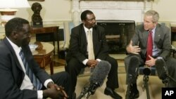 FILE - President George W. Bush, right, meets 2006 Democracy Award winners Alfred Taban of Sudan, left, and Reginald Matchaba-Hove of Zimbabwe, at the White House, June 27, 2006.
