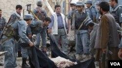 Polisi Afghanistan menutupi jenazah korban tewas dalam ledakan bom di Kunduz, Afghanistan utara.
