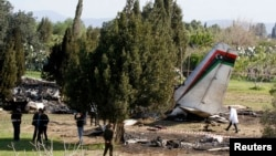 Penyidik berdiri di sekitar puing-puing pesawat militer Libya dekat kota Grombalia, Tunisia (21/2).