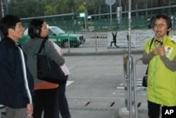香港區議會選舉候選人的助選員(右一)向市民講解候選人的參選理念